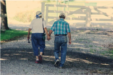 A couple holding hands walking on a farm path